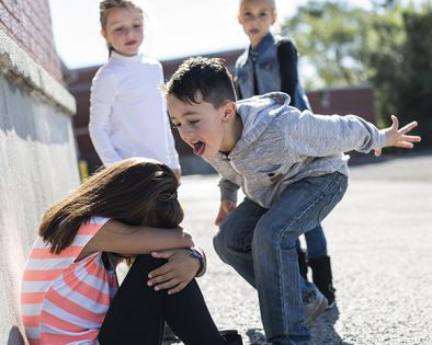 A group of children taunting (bullying) another child