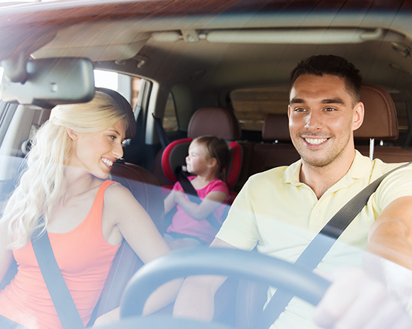 A family of three in a car, smiling