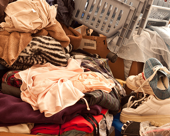 A disheveled pile of clothing and shoes