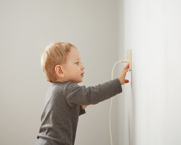 A toddler reaching out and touching an electrical plug that's plugged into the wall