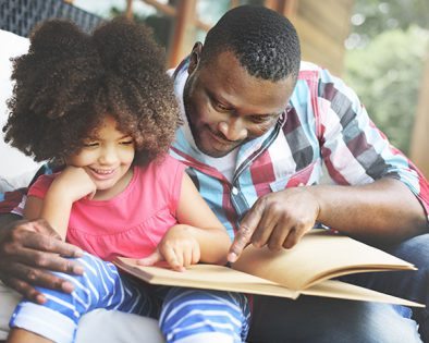 A father reading to his young daughter, who is seated next to him