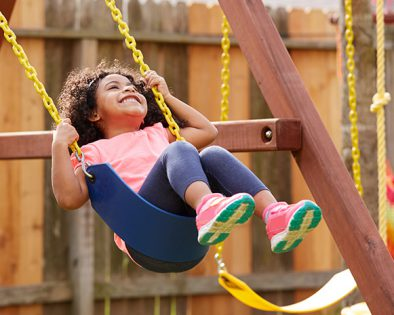 A young girl swinging on a swing set in a backyard
