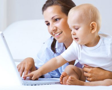 A mother helping her baby interact with a laptop