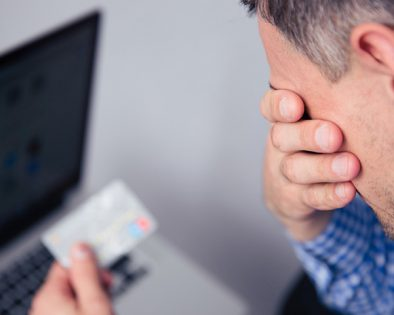 A man holding his credit card (in front of a laptop) with his face in his hands
