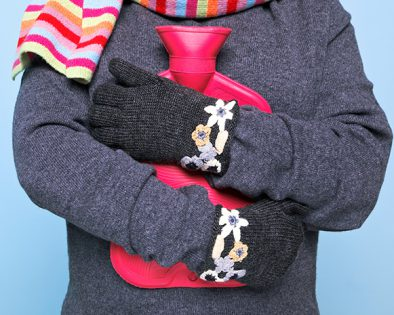A closeup of a bundled-up child hugging a pink hot water bottle