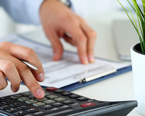 A closeup of a man using a calculator and taking note of his calculations