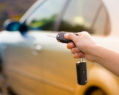 A closeup of someone's hand engaging a car's automatic opener
