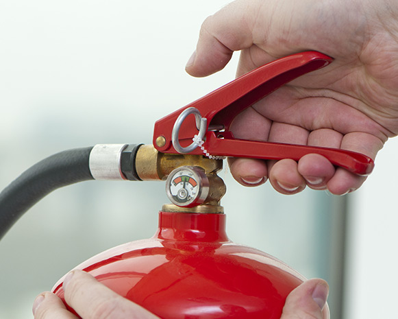 A closeup of a person gripping a fire extinguisher