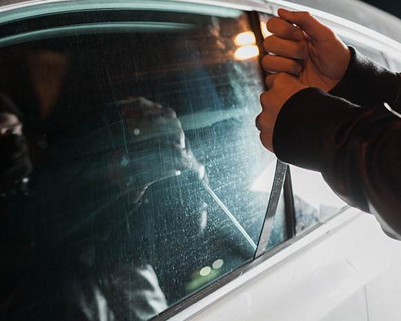 A closeup of somebody attempting to open a car window with a tool